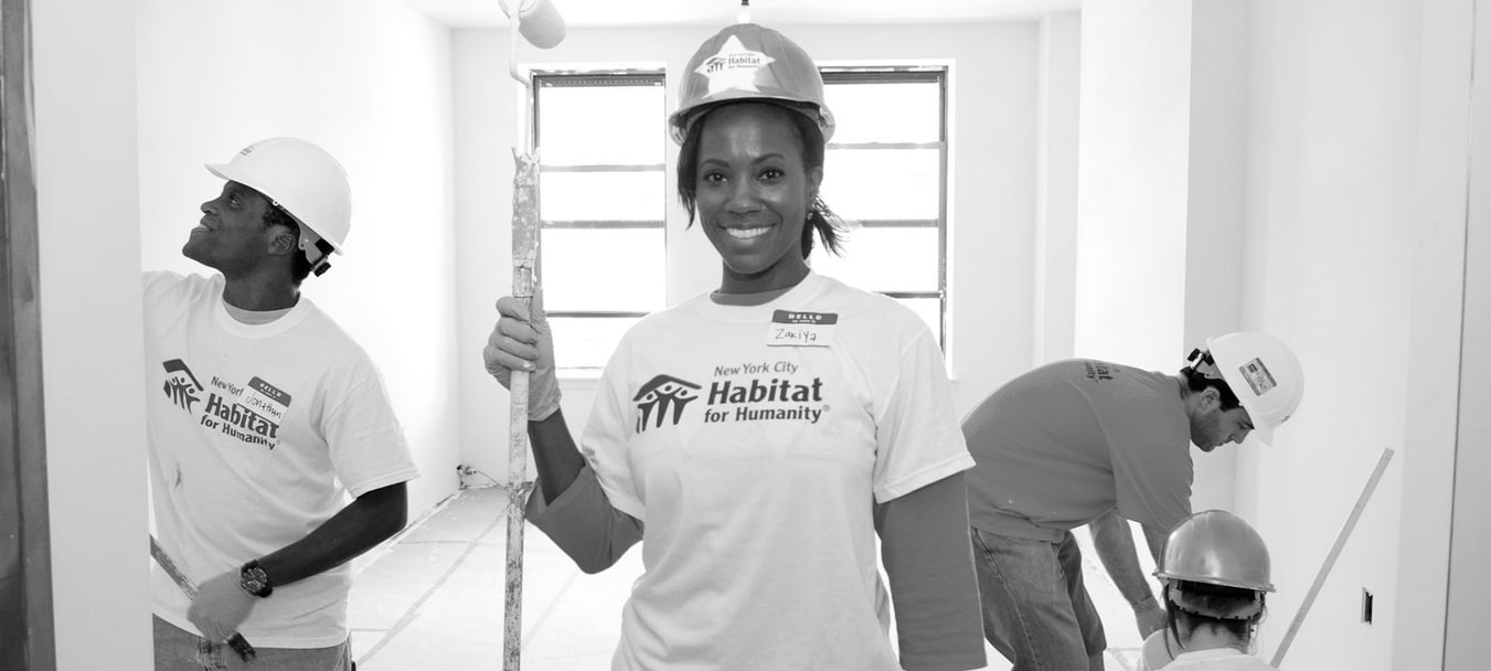 An on-site volunteer stands with a paint roller